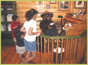 Picture of Smokey Bear reading his fan mail; children are viewing Smokey in the Information Center, located on the bottom floor of the Yates building.